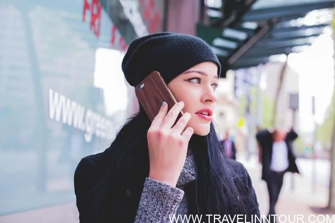 talking on phone e1577157877969 - 10 Solo Travel Tips for Beginners